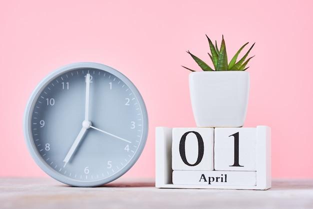 Calendario de bloques de madera con fecha 1 de abril, despertador y planta en rosa