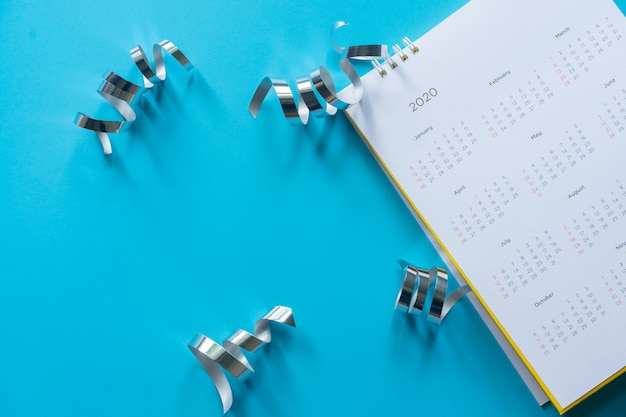 Calendario calendario 2020 sobre fondo de color azul con cinta plateada para feliz año nuevo 2020
