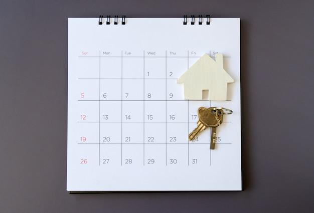 Calendario y casa en la mesa. día de compra o venta de una casa o pago de alquiler o préstamo.
