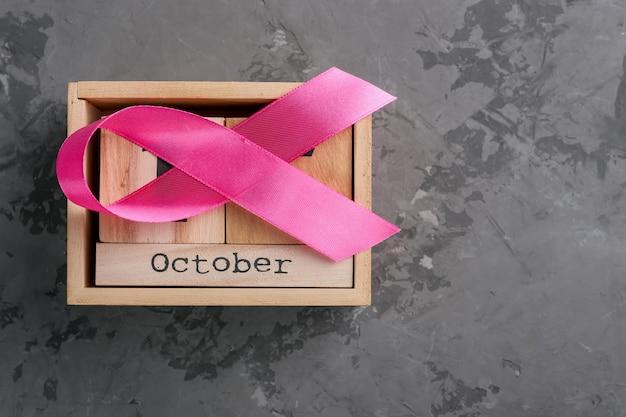 Calendario de cinta rosa y cubo de madera establecido para el 15 de octubre en una superficie de concreto, mes de concientización sobre el cáncer de mama