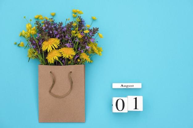 Calendario de cubos el 1 de agosto y las coloridas flores rústicas de campo en un paquete artesanal sobre fondo azul