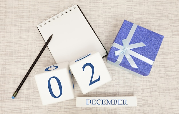 Calendario de cubos para el 2 de diciembre y caja de regalo, cerca de una libreta con un lápiz