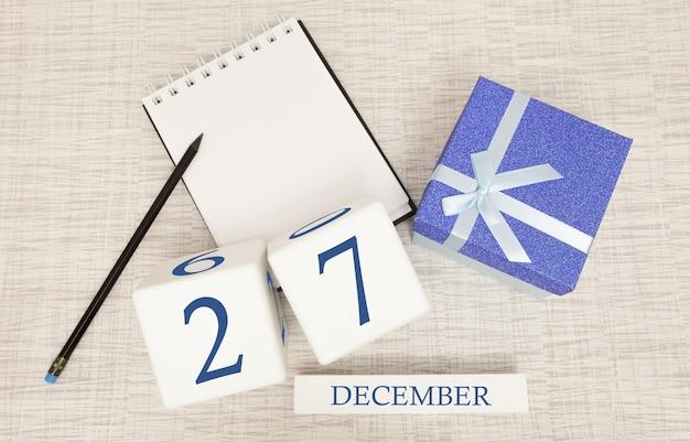 Calendario de cubos para el 27 de diciembre y caja de regalo, cerca de una libreta con un lápiz