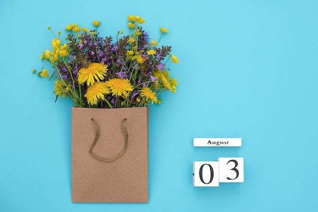 Calendario de cubos de madera el 3 de agosto y coloridas flores rústicas de campo en un paquete de arte ign