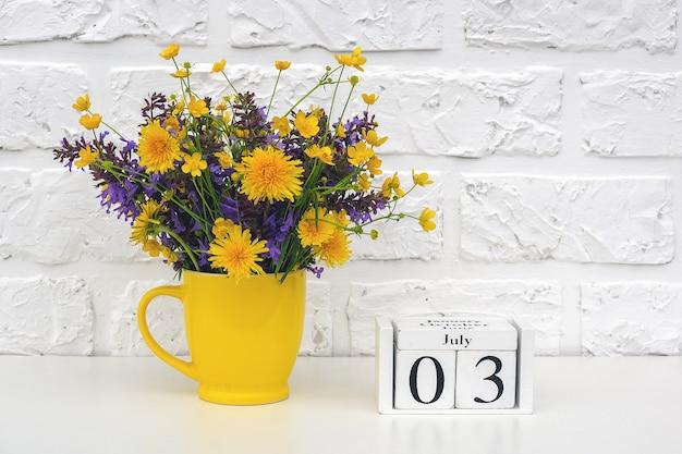 Calendario de cubos de madera el 3 de julio y taza amarilla con flores de colores brillantes contra la pared de ladrillo blanco.