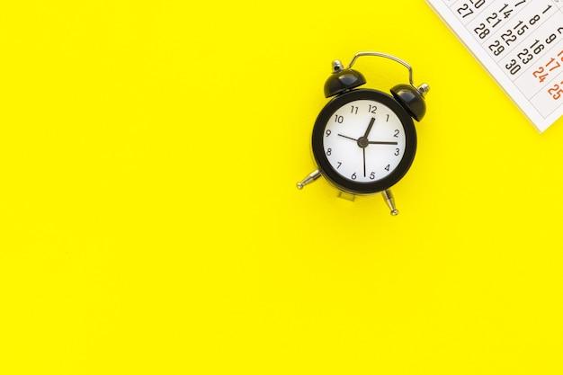 Calendario y despertador en amarillo planeación de fechas límite para reuniones de negocios o planificación de viajes