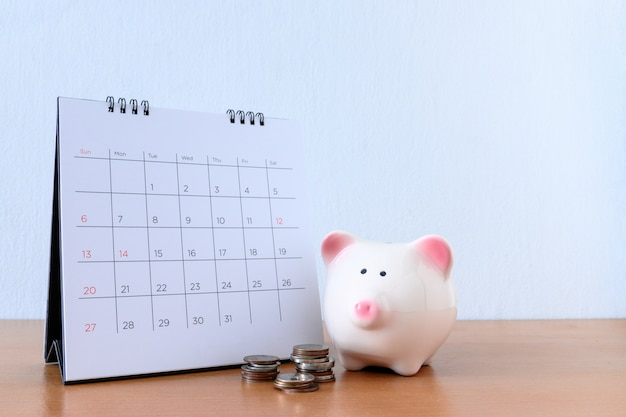 Calendario con días y alcancía en mesa de madera