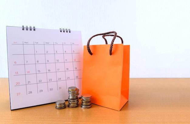 Calendario con días y bolsa de papel naranja en mesa de madera. concepto de compra