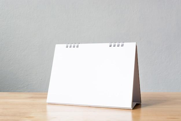 Calendario de escritorio en blanco en la mesa de madera.
