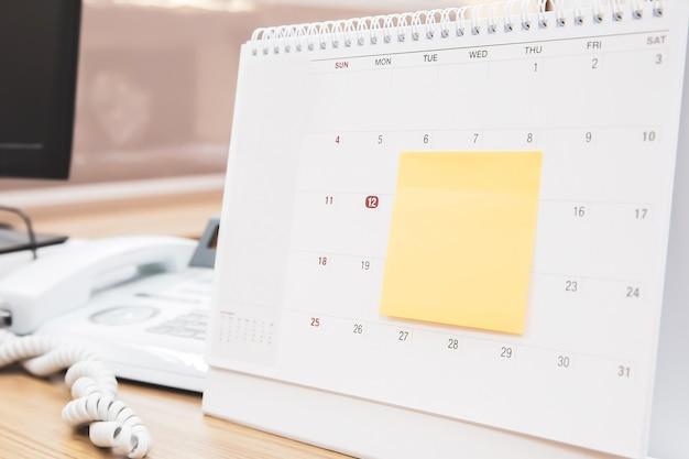 Calendario de escritorio en blanco con nota de papel.