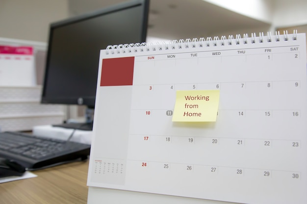 Calendario de escritorio en blanco de primer plano con nota de papel trabajando desde casa.
