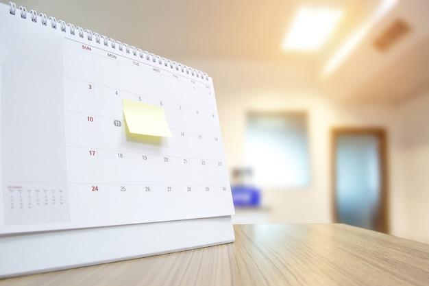 Calendario de escritorio en blanco de primer plano con nota de papel.