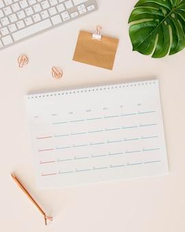 Calendario de escritorio plano con hoja de monstera y caja de lápices