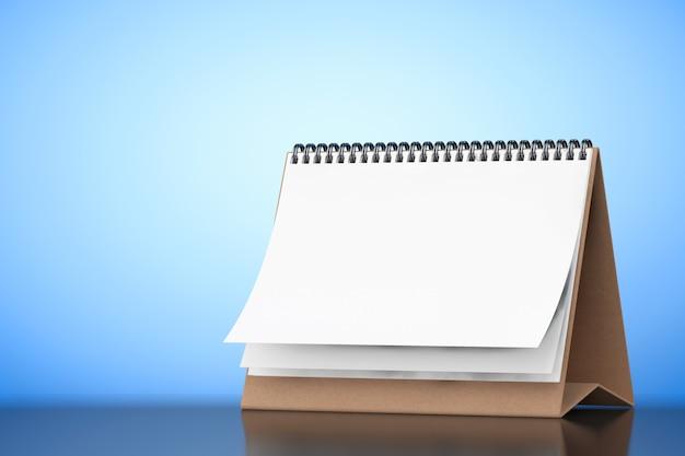 Calendario en espiral de escritorio de papel en blanco sobre un fondo azul. representación 3d