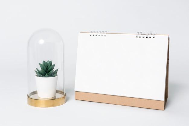 Calendario espiral de papel en blanco y plantas en florero para la plantilla de maqueta