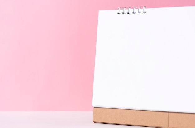 Calendario espiral del papel en blanco para la publicidad de la plantilla de la maqueta y la marca en fondo rosado.