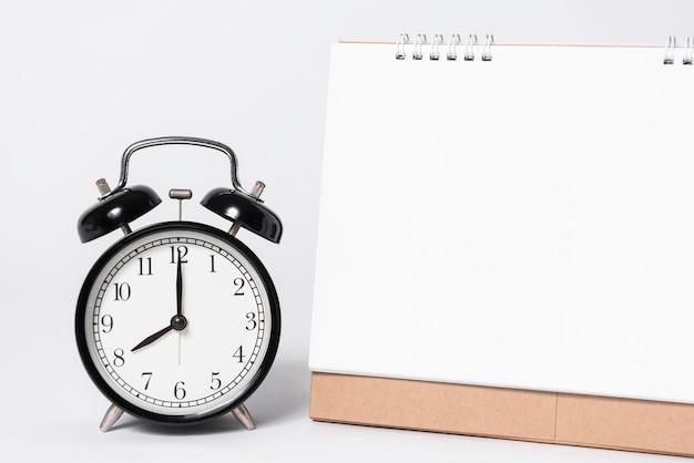 Calendario espiral de papel en blanco para la publicidad de la plantilla de la maqueta y marca con el reloj en fondo gris.