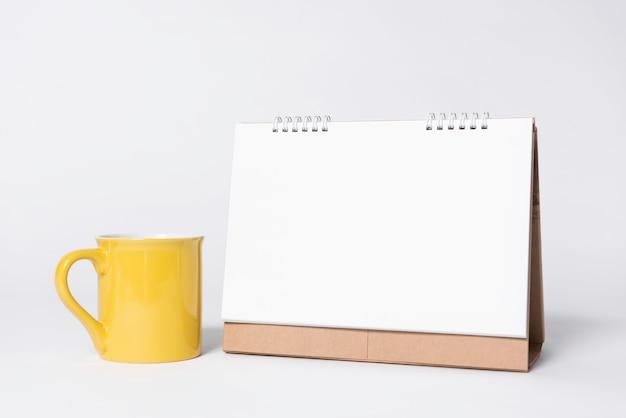 El calendario espiral del papel en blanco y la taza amarilla para la publicidad de la plantilla de la maqueta y el fondo de marcado en caliente.