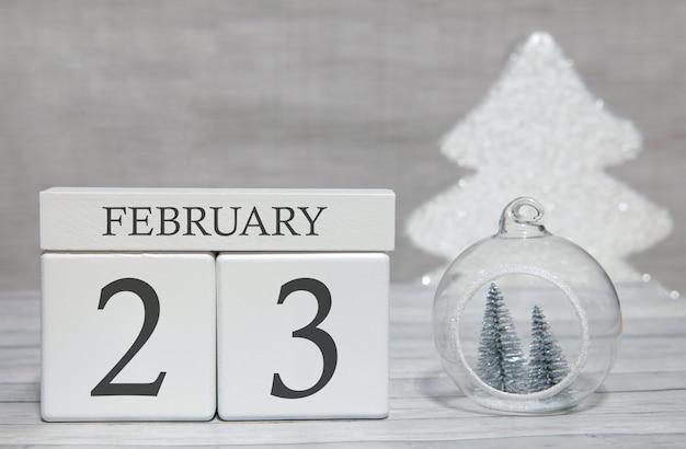 Calendario de forma de cubo para el 23 de febrero sobre superficie de madera y fondo claro