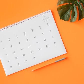 Calendario con lápiz y hoja de monstera