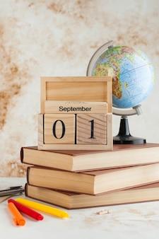 Calendario de madera el 1 de septiembre en una pila de libros, globo. concepto para el día del conocimiento, comienzo del año escolar.