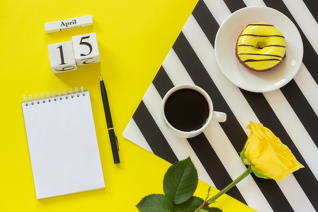 Calendario de madera 15 de abril. taza de café, rosquilla, rosa, libreta. concepto de lugar de trabajo con estilo