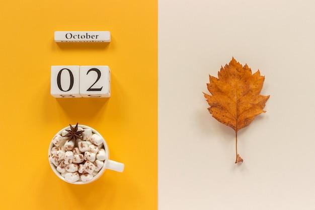 Calendario de madera 2 de octubre, taza de cacao con malvaviscos y hojas amarillas de otoño sobre fondo amarillo amarillento.