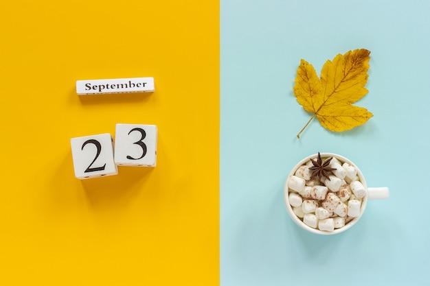 Calendario de madera 23 de septiembre, taza de cacao con malvaviscos y hojas amarillas de otoño sobre fondo azul amarillo.