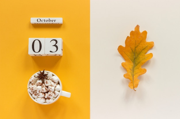 Calendario de madera 3 de octubre, taza de cacao con malvaviscos y hojas amarillas de otoño