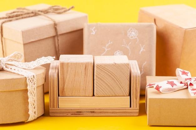 Calendario de madera en blanco vacío y cajas de regalo kraft en amarillo. maqueta para idea de celebración, venta o vacaciones.