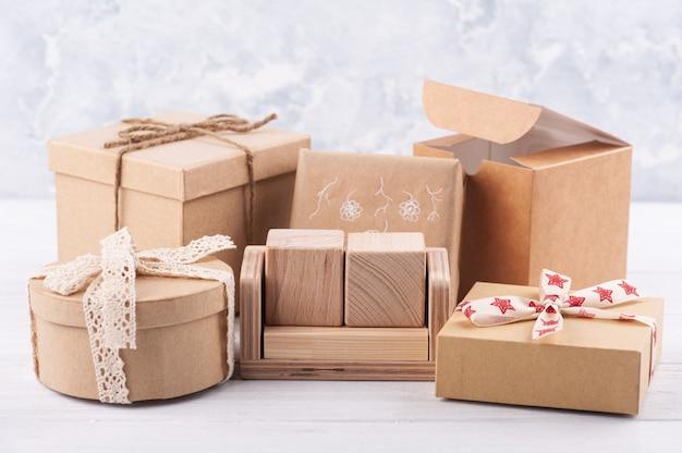 Calendario de madera en blanco vacío y cajas de regalo kraft en mesa blanca. maqueta para idea de celebración, venta o vacaciones.