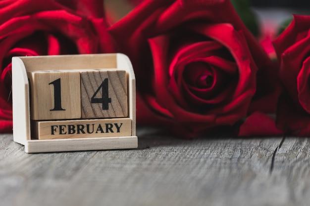 Calendario de madera colocado en un piso de madera gris y rosa roja, tema del día de san valentín