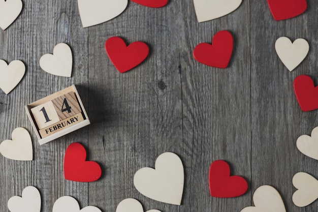 Calendario de madera y corazones de madera, blanco y rojo colocados en un piso de madera gris, vista superior y espacio de copia, tema del día de san valentín
