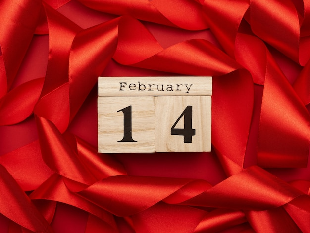 Calendario de madera con fecha 14 de febrero en cinta de seda roja, día de san valentín