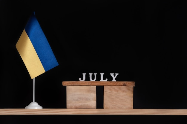 Calendario de madera de julio con bandera ucraniana sobre fondo negro. fechas en ucrania en julio.