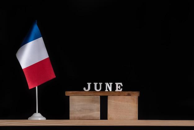 Calendario de madera de junio con bandera francesa sobre fondo negro. vacaciones de francia en junio.