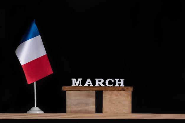 Calendario de madera de marzo con bandera francesa sobre fondo negro. vacaciones de francia en marzo.