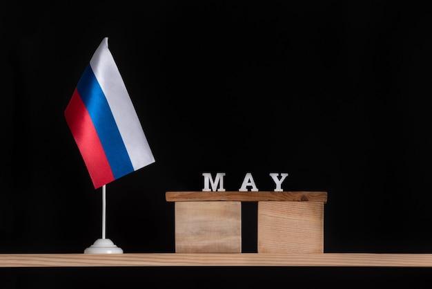 Calendario de madera de mayo con bandera rusa sobre fondo negro. fechas en rusia en mayo.