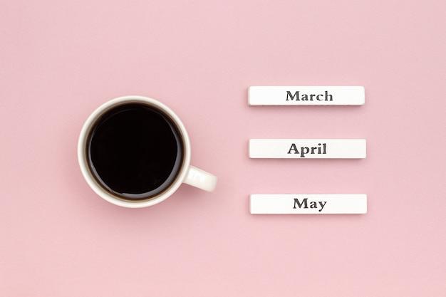 Calendario de madera meses de primavera marzo abril mayo y taza de café negro dirigido a mayo sobre fondo de papel rosa pastel.