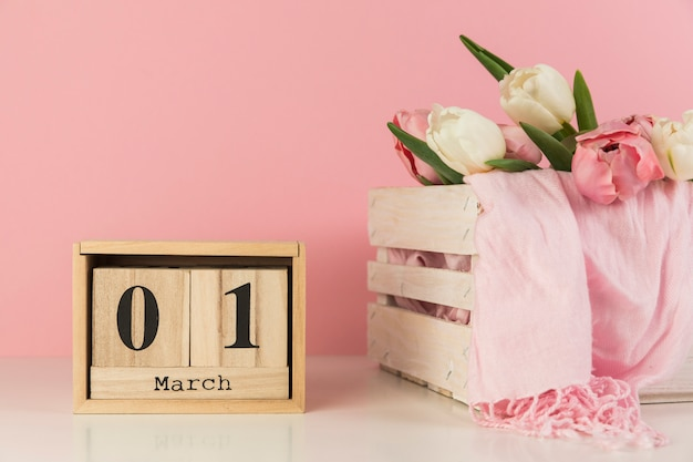 Calendario de madera que muestra el 1 de marzo cerca de la caja con tulipanes y bufanda sobre fondo rosa