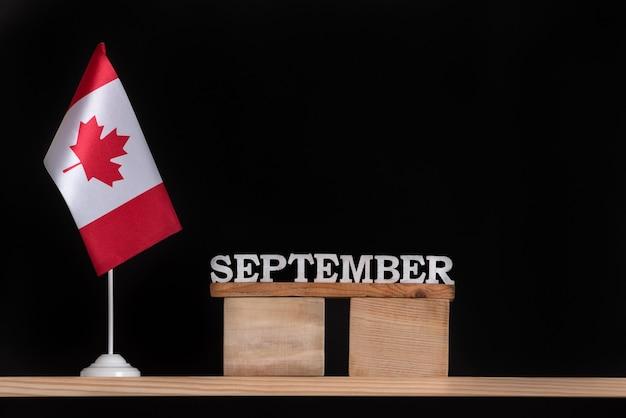 Calendario de madera de septiembre con bandera canadiense sobre fondo negro. vacaciones de otoño en canadá.
