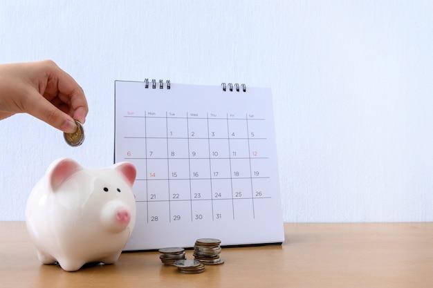 Calendario y mano infantil poniendo dinero de moneda en hucha