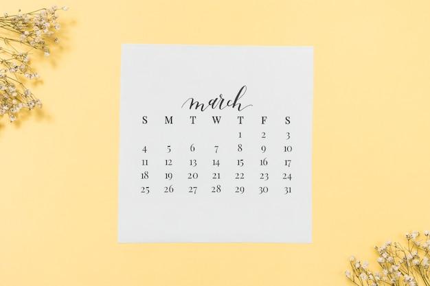 Calendario de marzo con ramas de flores en la mesa