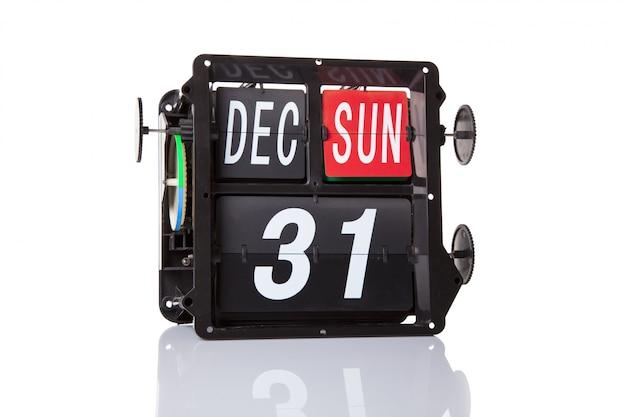 El calendario mecánico retro fecha 31 de diciembre, sobre un fondo blanco.