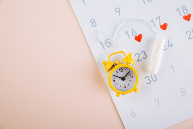 Calendario de menstruación con alarma amarilla y toallas sanitarias diarias sobre fondo rosa. días críticos de la mujer, concepto de protección de la higiene de la mujer.