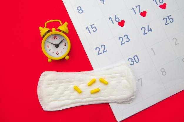 Calendario de menstruación con almohadillas, reloj despertador, píldoras anticonceptivas hormonales en rojo