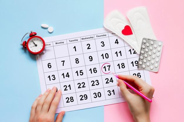 Calendario de la menstruación con almohadillas, reloj despertador, píldoras anticonceptivas hormonales.