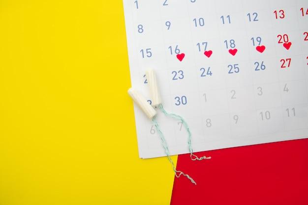 Calendario de menstruación con tampones de algodón. días críticos de la mujer, concepto de protección de la higiene de la mujer
