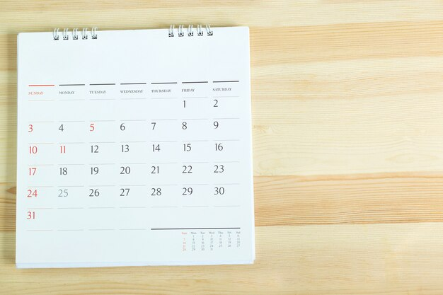 Calendario en la mesa de madera. espacio de copia vacío para el texto. concepto para la línea de tiempo ocupada organizar el horario