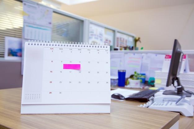 Calendario con nota de papel en el escritorio de oficina para el planificador de eventos.